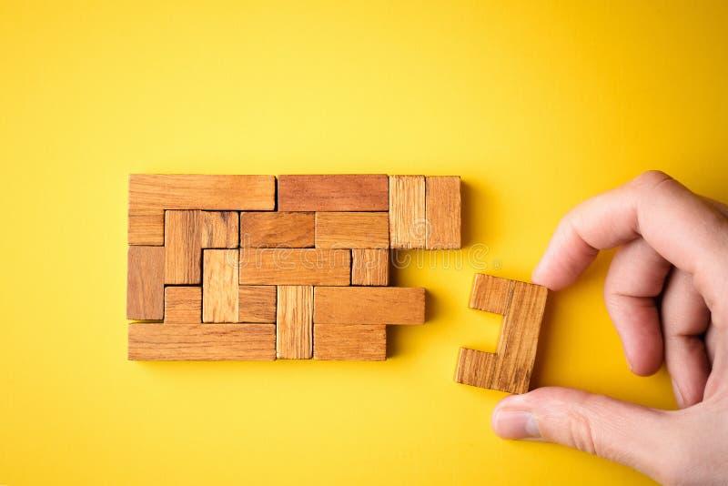 Kobieta ręka stawiający drewniani bloki dla kończyć zadanie obrazy stock