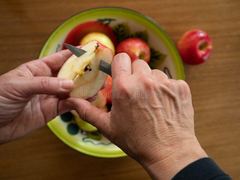 Kobieta Rdzeniuje Apple z Organicznie jabłkami w tle fotografia royalty free