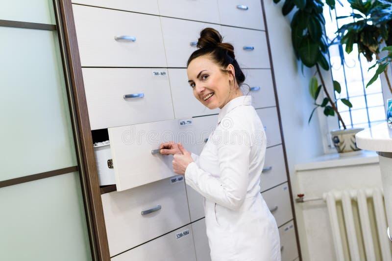 Kobieta recepcjonista w medycznych żakietów stojakach obraz royalty free