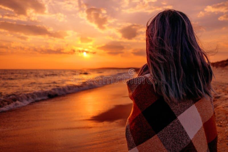 Kobieta relaksuje blisko morza przy zmierzchem obrazy royalty free