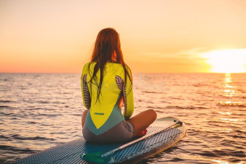 Kobieta relaksuje dalej stoi up paddle deskę, spokojny morze z ciepłymi zmierzchów kolorami obraz stock