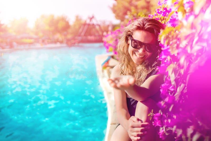 kobieta relaksuje i sunbathing przy basenem poj?cia t?a ramy piasek seashells lato zdjęcie royalty free