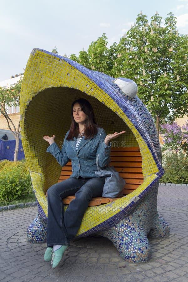 Kobieta relaksuje na śmiesznej ławce zdjęcie stock