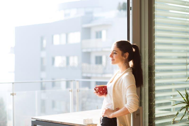 Kobieta relaksuje na balkonowej trzyma filiżance kawy lub herbacie obrazy stock