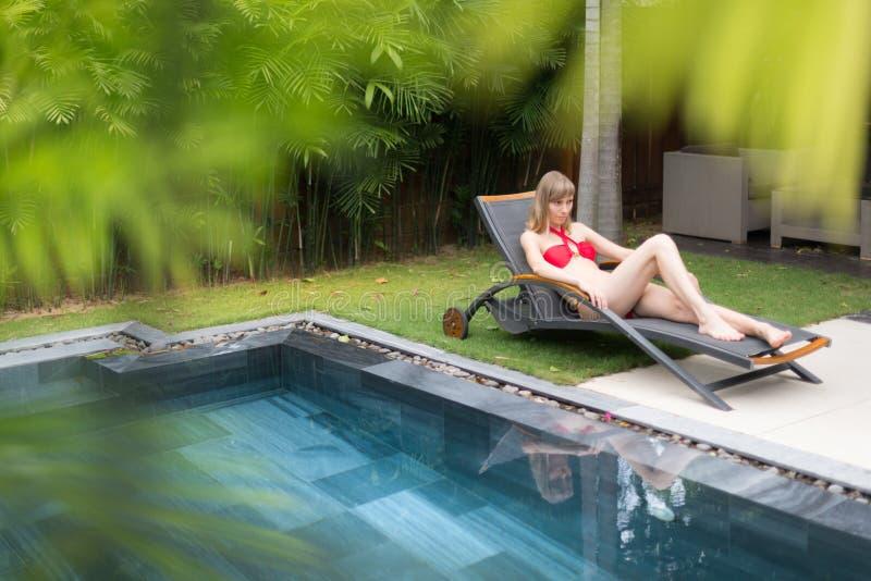 Kobieta relaksuje na bryczki longue pobliskim basenie obraz royalty free