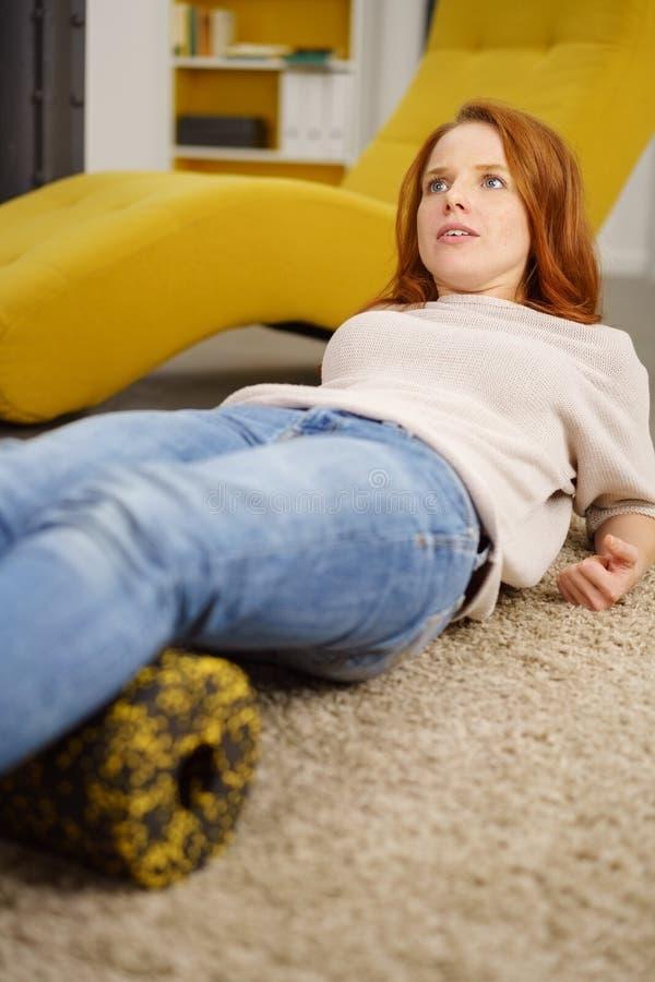 Kobieta relaksuje na dywanie z podgłówek poduszką zdjęcie stock