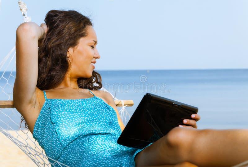 Kobieta relaksuje na hamaku i używa cyfrową pastylkę zdjęcia royalty free