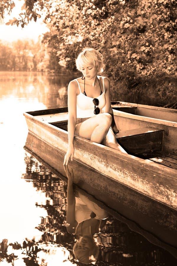 Kobieta relaksuje na rocznik drewnianej łodzi. zdjęcia royalty free