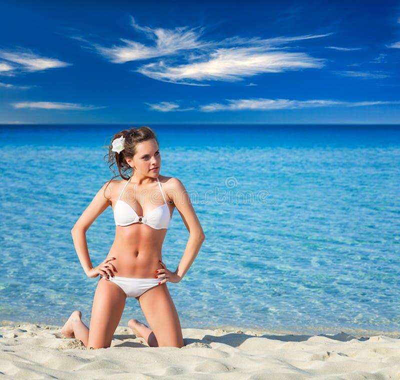 Kobieta relaksuje na tropikalnej plaży w białym pływanie kostiumu zdjęcia stock