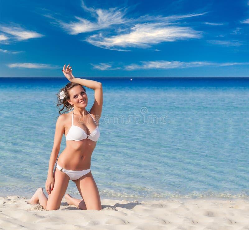 Kobieta relaksuje na tropikalnej plaży w białym pływanie kostiumu fotografia stock