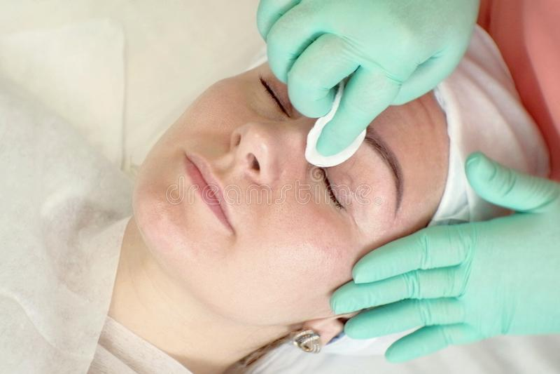 Kobieta relaksuje na zdrowie procedurach w piękno salonie Ręki beautician który czyści dziewczyny twarz od makeup gąbka obrazy royalty free