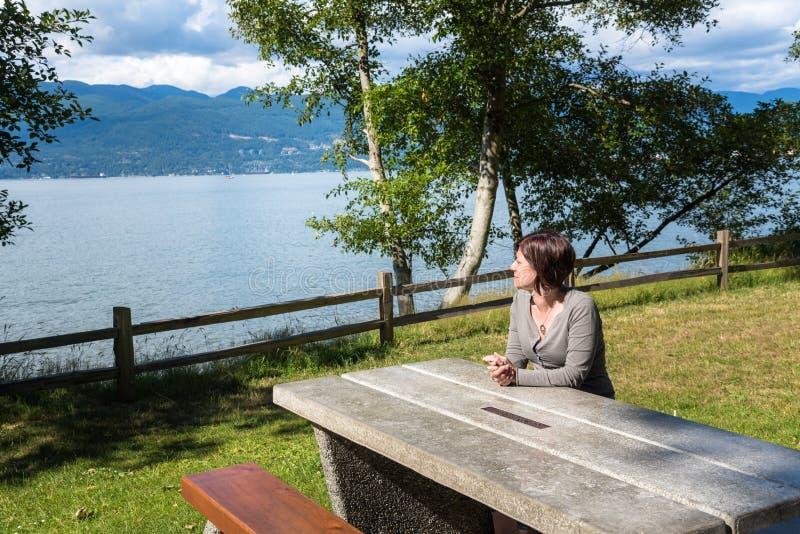 Kobieta Relaksuje scenerię w Nabrzeżnym Parkon Pogodny letni dzień i Podziwia zdjęcia stock