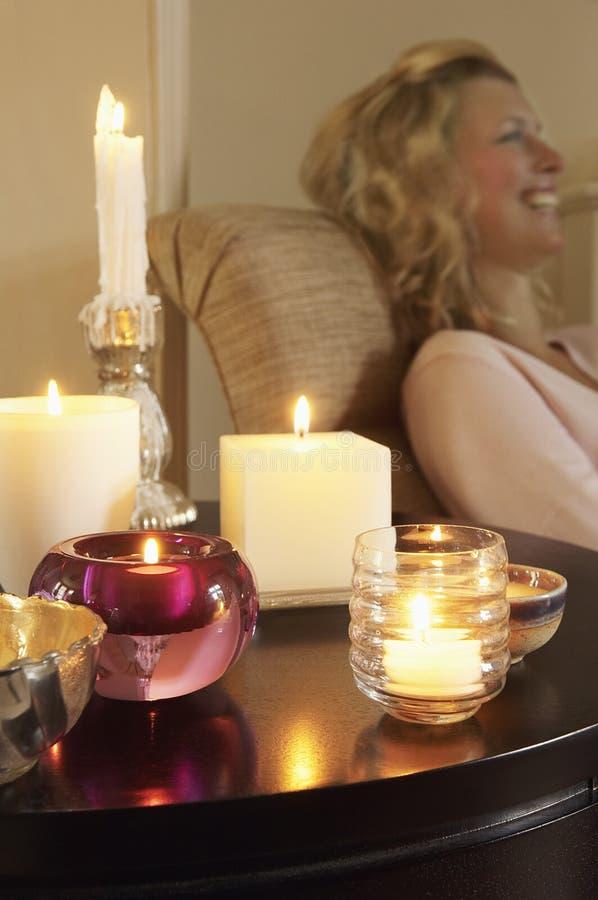 Kobieta Relaksuje stołem Z Zaświecać świeczkami zdjęcie royalty free
