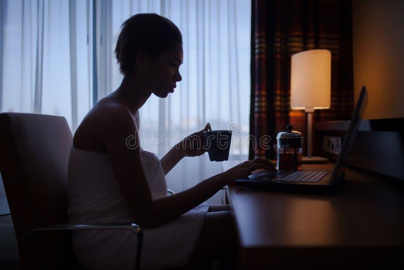 Kobieta relaksuje w domu po skąpania z laptopem zdjęcie royalty free