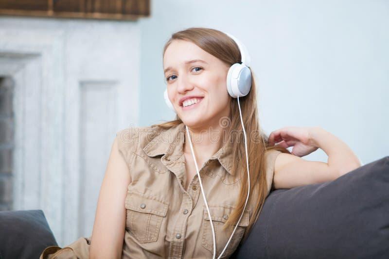 Kobieta relaksuje w kanapie cieszy się muzykę w hełmofonach w domu, ono uśmiecha się zdjęcie stock
