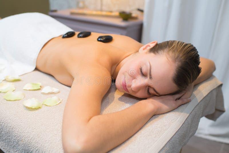 Kobieta relaksuje w zdroju salonie z gor?cymi kamieniami na ciele fotografia royalty free