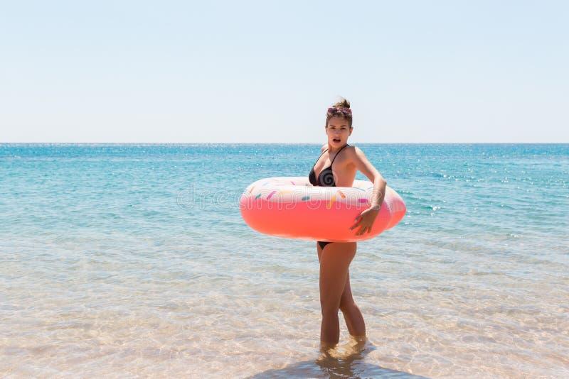 Kobieta relaksuje z nadmuchiwanym pierścionkiem na plaży szokująca lub zdziwiona dziewczyna w zimnym morzu Wakacje letni i urlopo fotografia stock