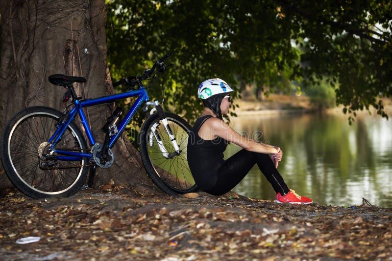 Kobieta relaksuje z rowerem jeziorem zdjęcia stock