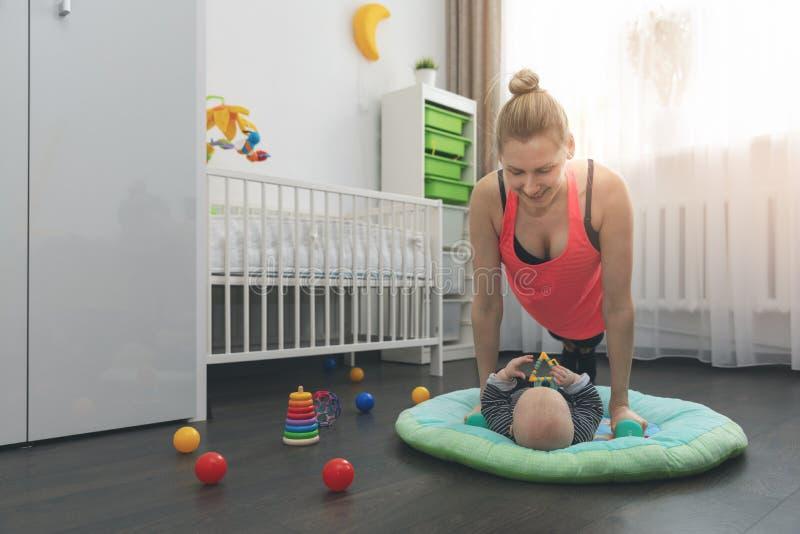 Kobieta robić pcha ups w domu podczas gdy bawić się z jej małym dzieckiem obraz royalty free