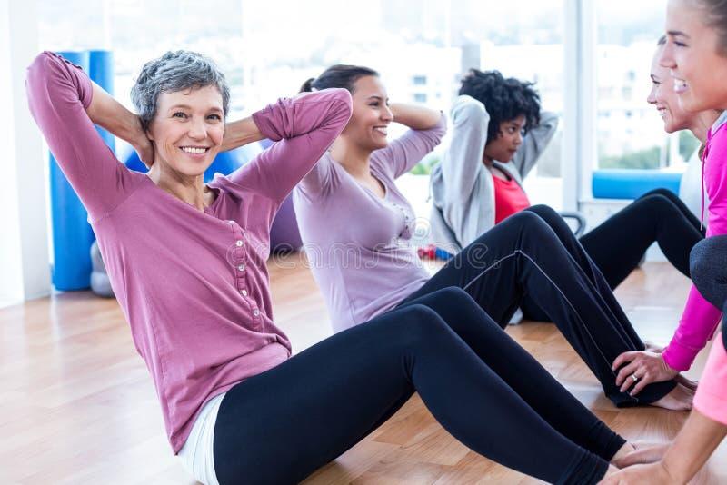 Kobieta robić siedzi podnosi z przyjaciółmi przy sprawności fizycznej studiiem zdjęcie royalty free