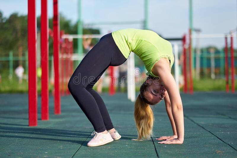 Kobieta robi ćwiczenie mostowi Rozciąganie gimnastyczki lub dansera szkolenia pociągi w treningów sportach gruntują obrazy stock