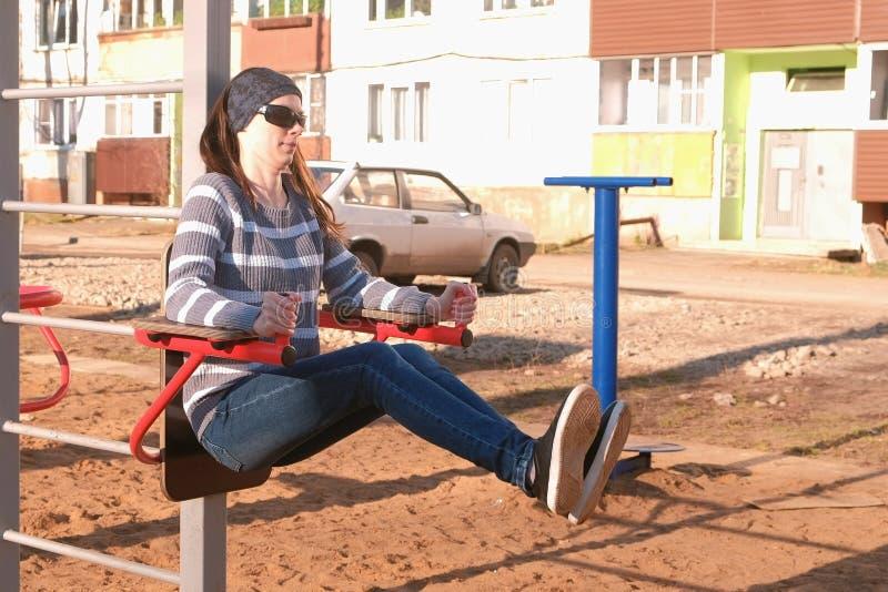 Kobieta robi ćwiczeniom na barze w miasto jardzie wśród wielo- kondygnaci na boisku zdjęcie royalty free