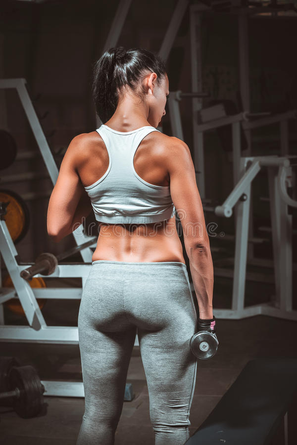 Kobieta robi ćwiczeniom z dumbbell w gym obrazy royalty free