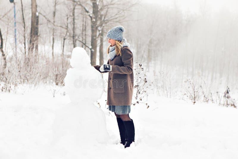 Kobieta robi bałwanu w zima czasie obrazy royalty free