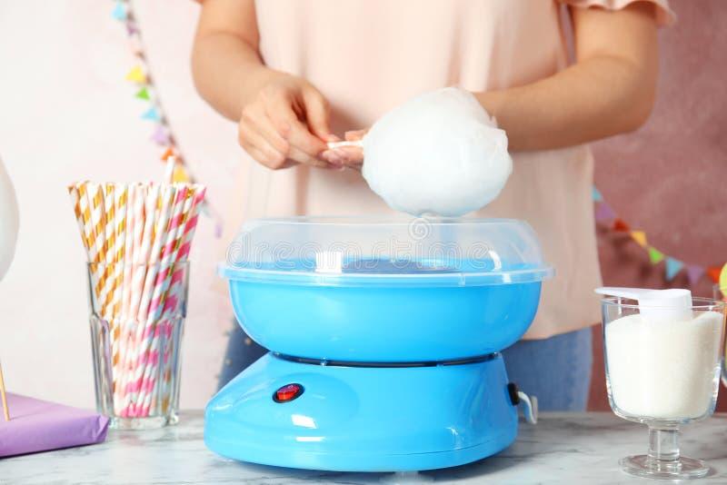 Kobieta robi bawełnianemu cukierkowi używać nowożytną maszynę przy stołem zdjęcie stock