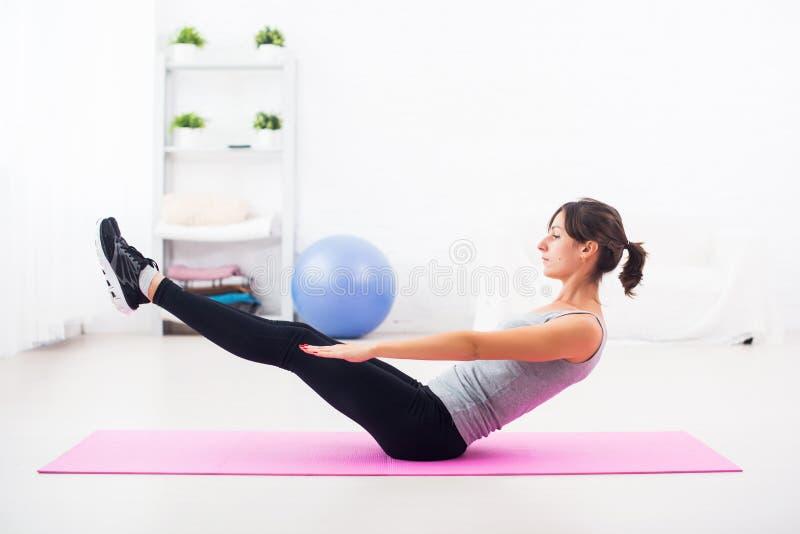 Kobieta robi brzusznemu ćwiczeniu na macie rozciąga pilates joga sprawność fizyczną w domu, sport, trenuje zdjęcie stock