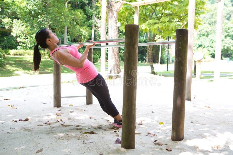 Kobieta robi ciągnieniu up na ćwiczenie barze w parku zdjęcie royalty free