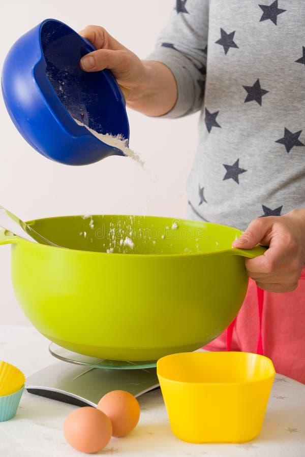 Kobieta robi ciastu dla muffins Mieszać mąkę, cukier, jajka i innych składniki od kolorowych pucharów, Domowej roboty jedzenie, p zdjęcie stock