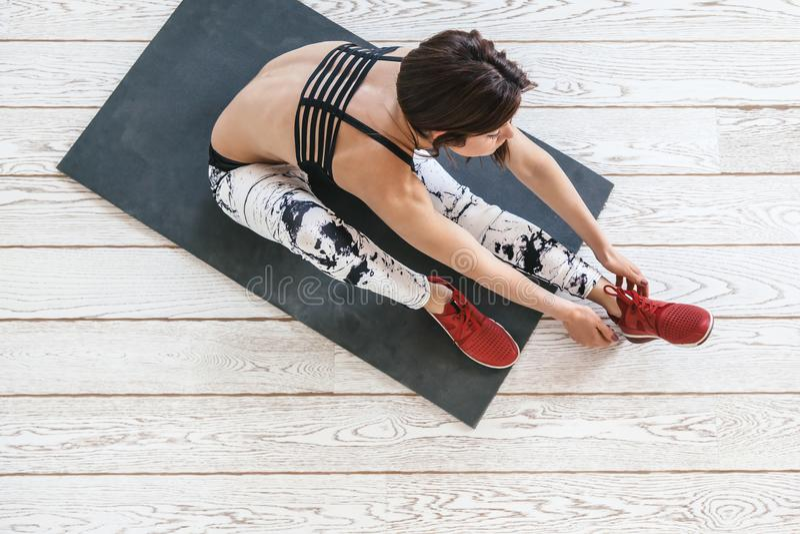 Kobieta robi dysponowanemu ćwiczeniu na białej podłoga obrazy stock