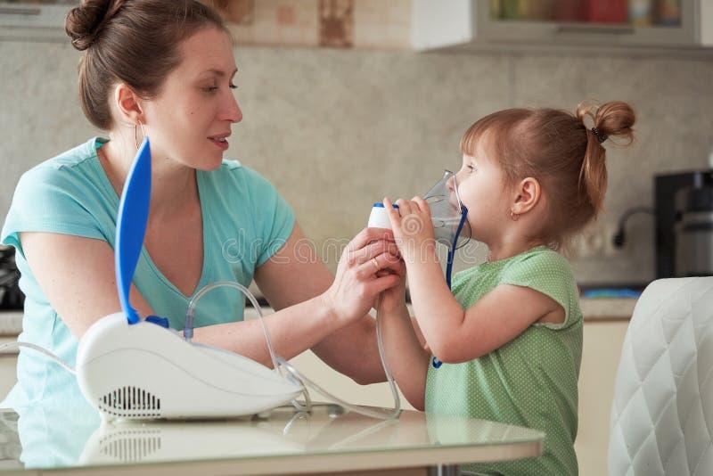 Kobieta robi inhalacji dziecko w domu przynosi nebulizer maskę jego twarz wdycha opary lekarstwo dziewczyna 2th lat confusedly obraz royalty free
