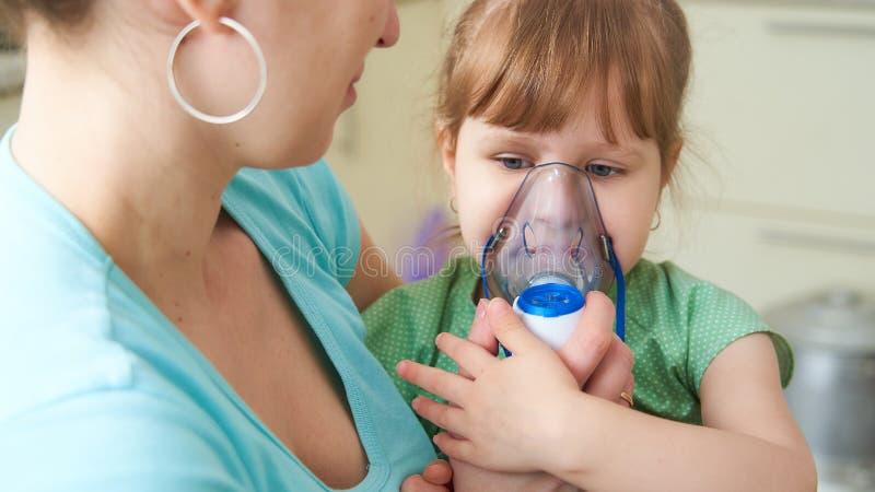 Kobieta robi inhalacji dziecko w domu przynosi nebulizer maskę jego twarz wdycha opary lekarstwo dziewczyna 2th lat confusedly obrazy royalty free