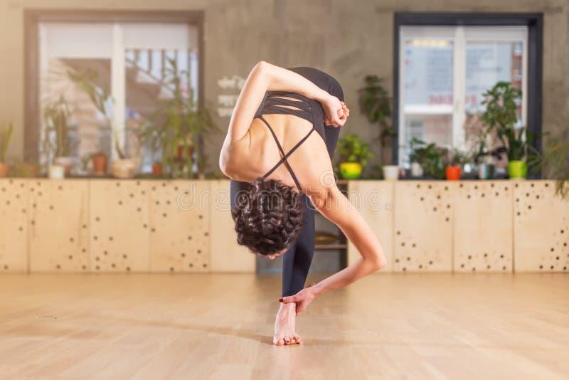 Kobieta robi joga, ćwiczący, trenujący w gym rozciągania chyleniu naprzód stoi na jeden nodze obraz stock