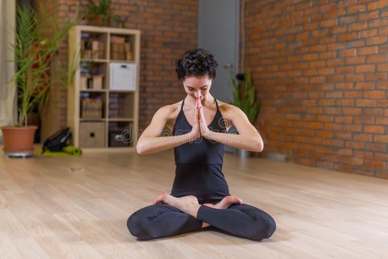 Kobieta robi joga medytuje w pełnej lotos pozie z rękami w Namaste w studiu obraz stock
