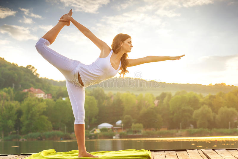 Kobieta robi joga na jeziorze - piękni światła zdjęcia stock