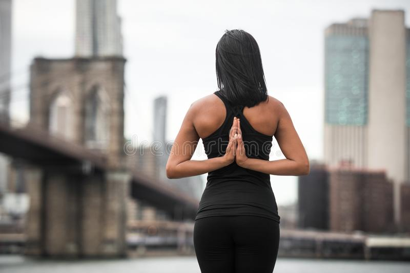 Kobieta robi joga pozie z rękami na plecy w Miasto Nowy Jork parku Joga klas pojęcie obraz stock