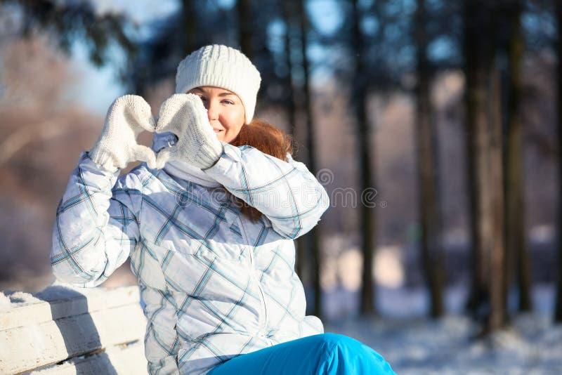 Kobieta robi kierowemu kształtowi z białymi mitynkami w świetle słonecznym przy zimą obrazy royalty free