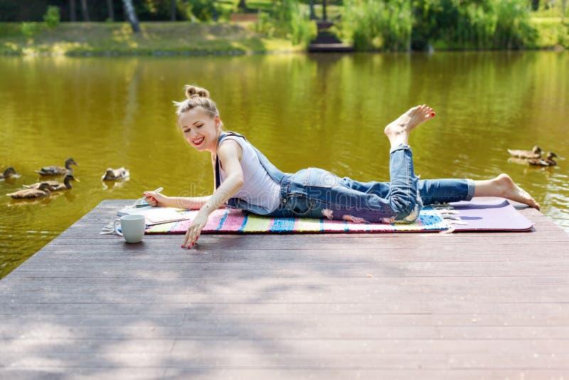 Kobieta robi planom, bierze notatki w kalendarzu, pisze w jej dzienniczka lying on the beach na molu lub pije gorącą kawę, Rojeni obraz stock