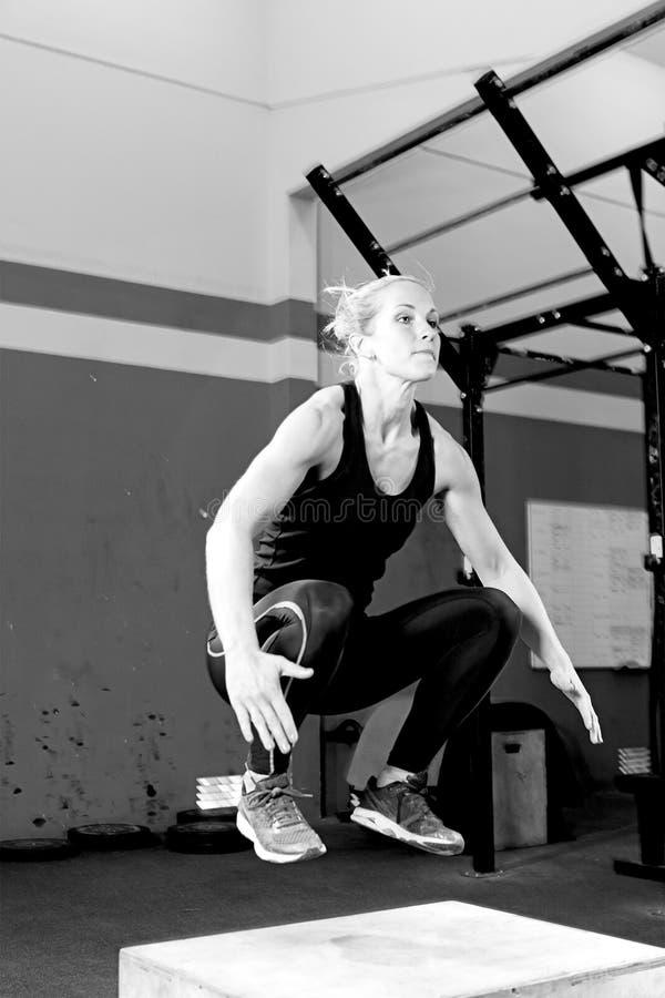 Kobieta robi pudełkowatemu skoku ćwiczeniu - crossfit trening zdjęcia royalty free