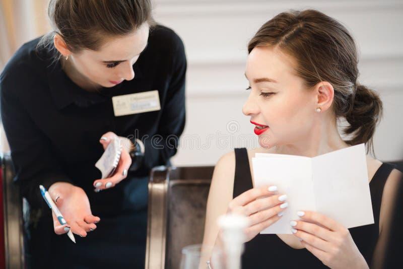 Kobieta robi rozkazowi od kelnerka menu fotografia royalty free