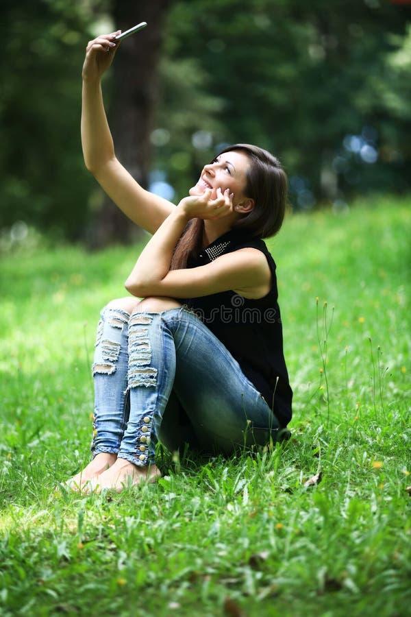 Kobieta robi selfie i relaksuje outdoors patrzeć szczęśliwy i uśmiechnięty obrazy stock