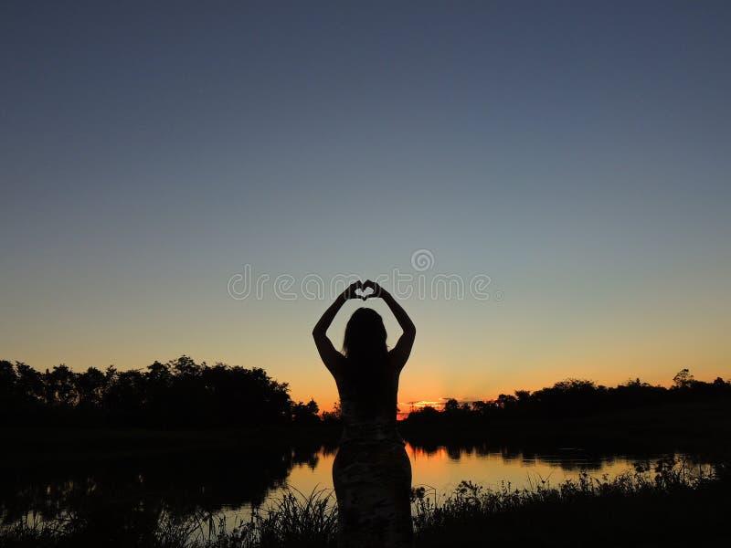 Kobieta robi sercu z rękami przy zmierzchem zdjęcie stock