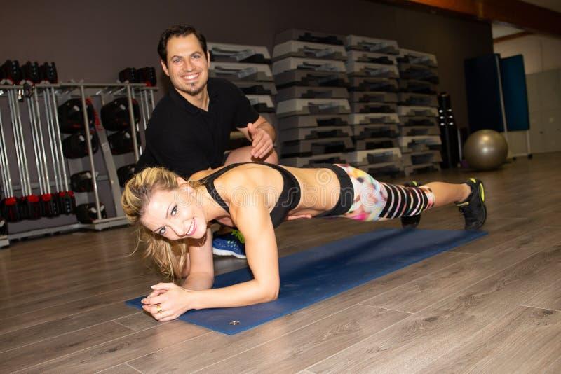 Kobieta robi sport sprawności fizycznej indoors i styl życia pojęcie z mężczyzną trenujemy instruktora zdjęcie royalty free