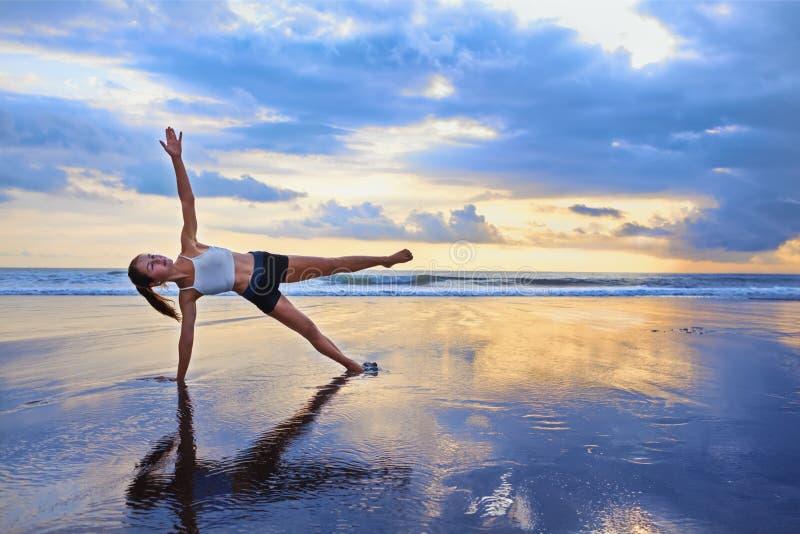 Kobieta robi sporta ćwiczeniu na zmierzch plaży obraz royalty free