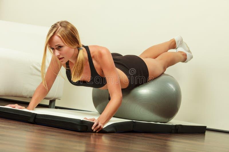 Kobieta robi sprawności fizycznej ćwiczy z dysponowaną piłką zdjęcie stock