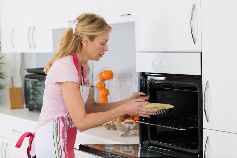 Kobieta robi wypiekowemu umieszcza tortowi w piekarniku fotografia stock