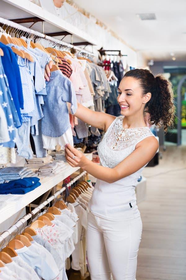 Kobieta robi zakupy błękitnego dziecka odzież obrazy stock